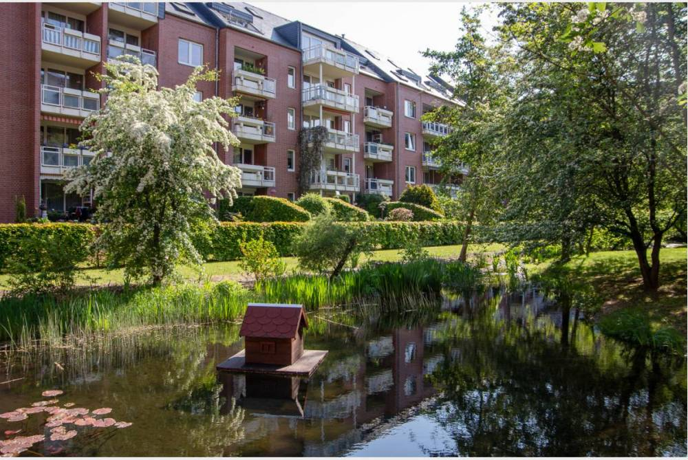 grüner Innenhof mit Teichanlage